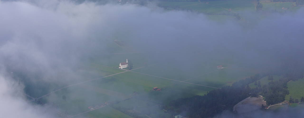 Our church St. Coloman in the Fog, Schwangau in the Background