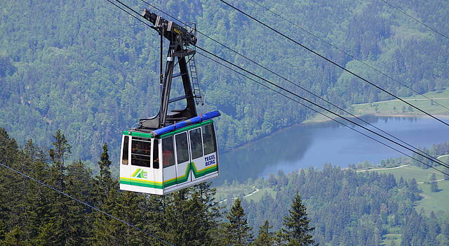 Cabin of the Tegelberg cable car with lake Schwansee in the background