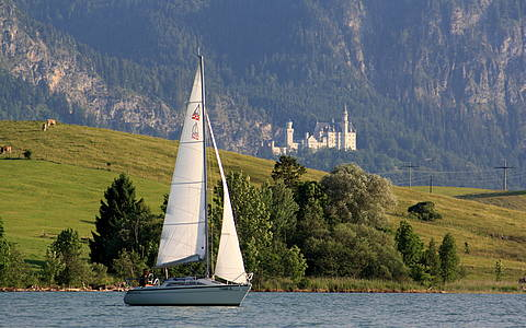 Sailingboat on lake Forggensee with Neuschwanstein castle in the background